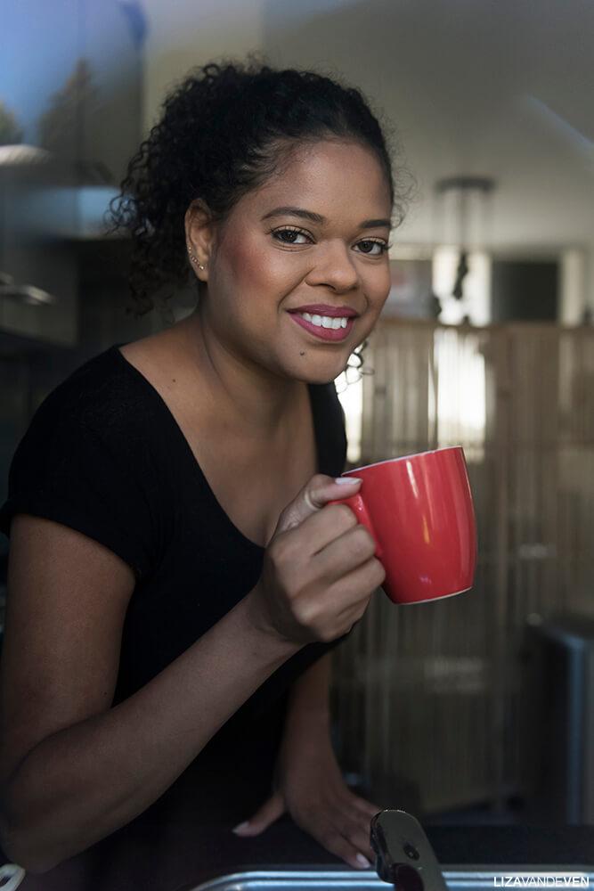 Maite met kopje koffie achter het raam