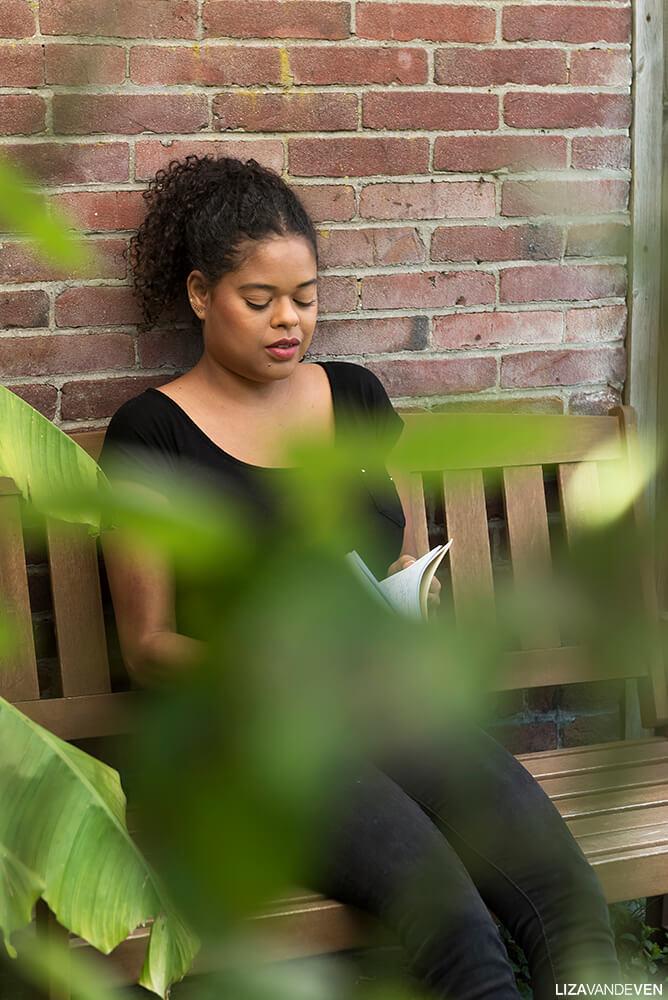 Maite met haar notitie boek op haar favoriete plek in de tuin