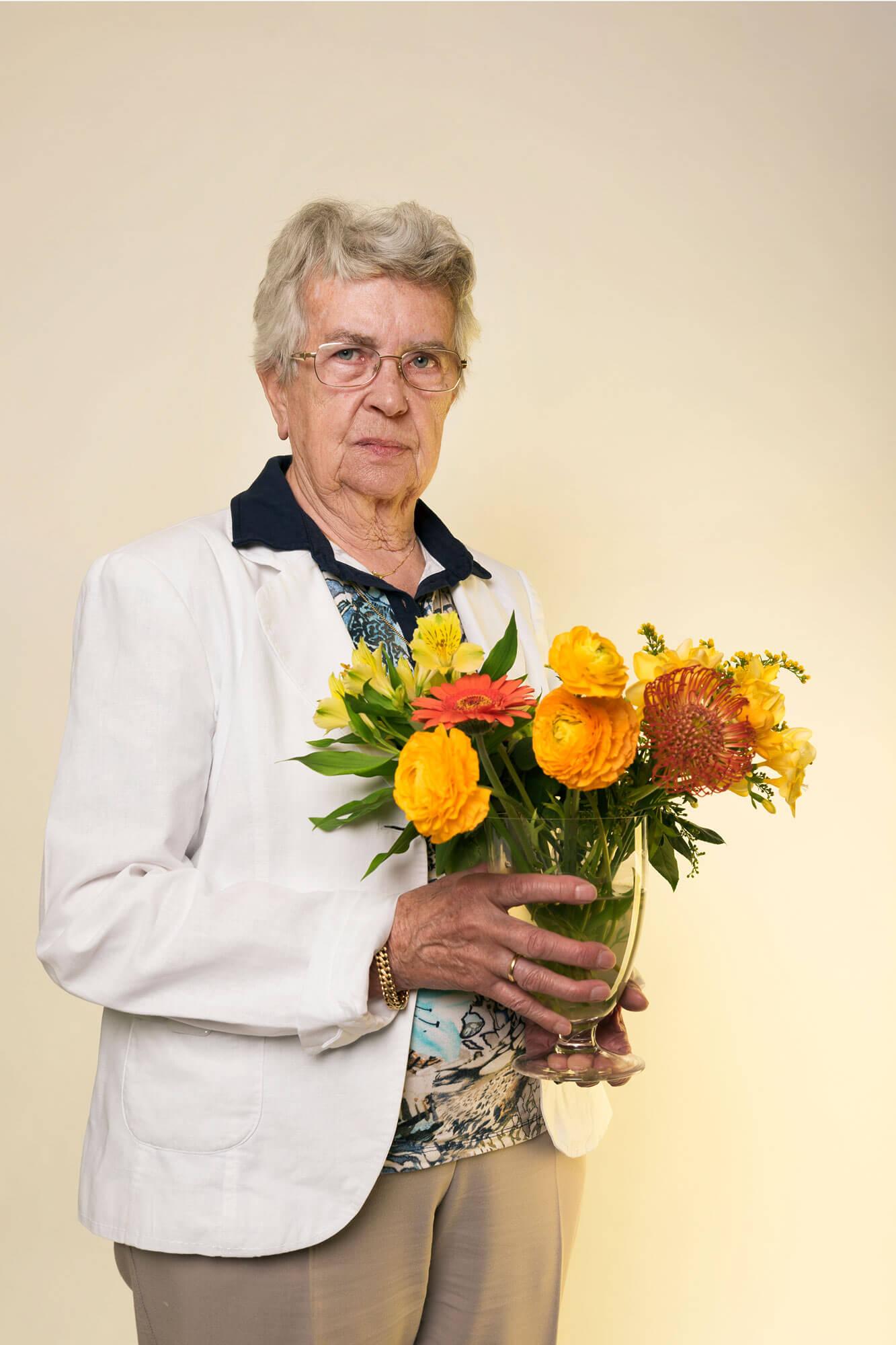 portret Mina met volle bos bloemen in vaas