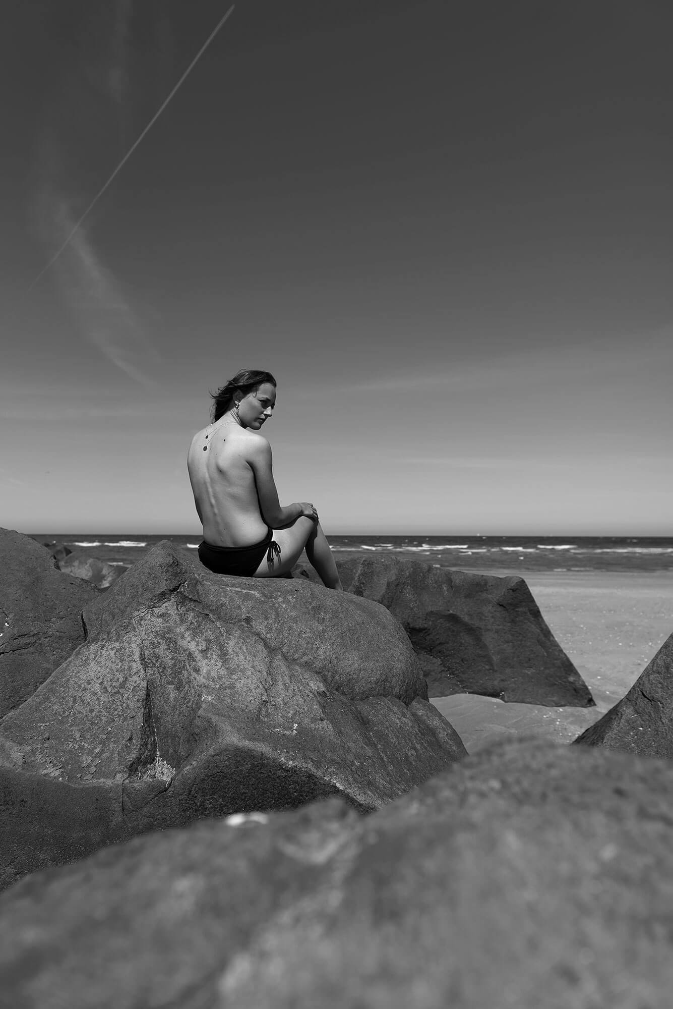 Beach day model blote rug zwart wit rotsen